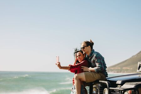 Woman taking selfie with her boyfriend at the beach. Couple standing by their car taking self portrait using a smartphone.