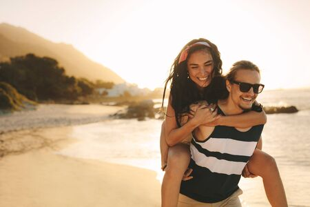 Young man and woman on vacation on a beautiful summer's day. Happy man carrying a woman on his back walking on beach.