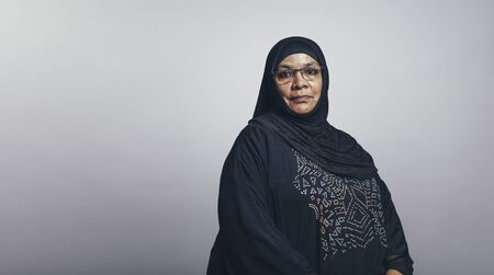 Arabic woman in eyeglasses and black hijab looking at camera. Senior muslim woman in hijab isolated on grey background. Stockfoto