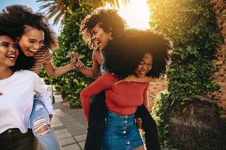 Heureuses jeunes femmes s'amusant dans la rue de la ville. Groupe d'amis multiethniques profitant du plein air. Des femmes s'emparent de ses amis.