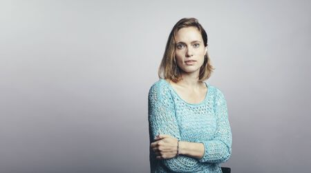 Businesswoman standing against grey background. Woman with short brown hair looking at camera with her arms crossed. Imagens