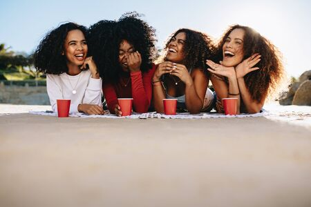 Group of young female friends hanging out at the beach. Cheerful mixed race women lying on beach with cold drinks.