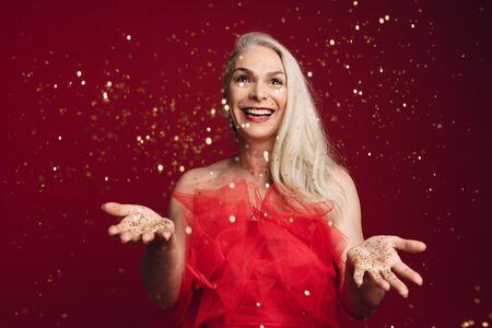 Mujer senior emocionada lanzando brillos en estudio. Mujer mayor caucásica que juega con la estrella dorada brilla sobre fondo rojo.