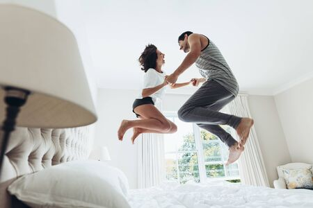 Man and woman holding hands and jumping together on bed. Couple having fun in bedroom.