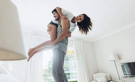 Young man standing on bed and carrying his girlfriend on his shoulder. Couple in playful mood in bedroom. Stock fotó