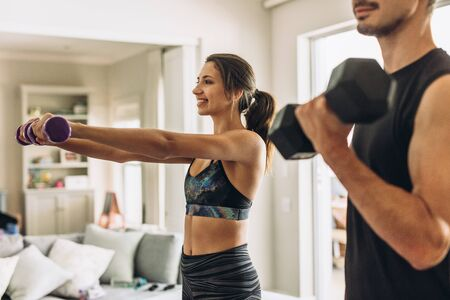 Healthy young couple doing exercises with dumbbells at home. Fit young woman with man doing weights workout indoors in living room. 스톡 콘텐츠 - 127399362