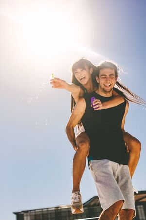 Man piggybacking his girlfriend on a summer day. Woman playing with soap bubble.