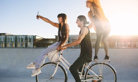 Friends on bike posing for a selfie. Young man sitting on bike with female friends on a sunny day.