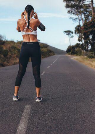 Vista trasera de una mujer joven de pie en una carretera vacía preparándose para correr. Mujer deportiva lista para su entrenamiento matutino. Foto de archivo