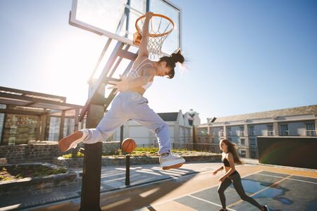Two young women playing basketball on street court on a sunny day. Women playing a streetball game outdoors.