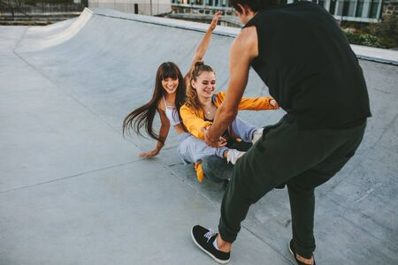 Two girls sitting on skateboard being pulled by male friend at skate park. Group of friends having hanging out at skate park. Фото со стока