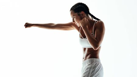 Fitness woman doing boxing workout. Female practicing boxing, throwing a punch in front against white background.