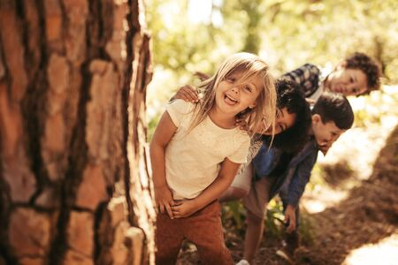 Group of kids standing in row and peeking behind a tree outdoors. Children playing hide and seek in a park. Reklamní fotografie