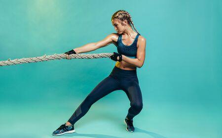 Mujer joven resistente que ejercita con la cuerda que lucha en estudio. Mujer de deportes saludables que se resuelve con la cuerda de batalla sobre fondo azul.