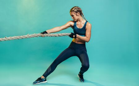 Tough young woman exercising with battling rope in studio. Healthy sports woman working out with battle rope over blue background. Stockfoto