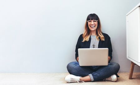 Woman entrepreneur working on laptop sitting at home. Smiling woman sitting on the floor at home using a laptop computer.