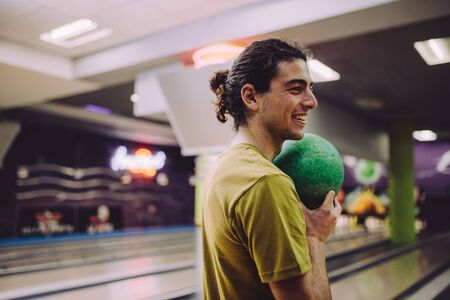 Stylish young man standing at bowling alley with ball at hand. Caucasian man with ball in bowling club. Stok Fotoğraf