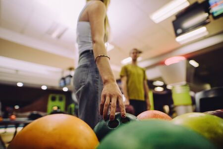 Woman choosing a bowling bowl. Close-up of female hand picking up a ball at bowling club.
