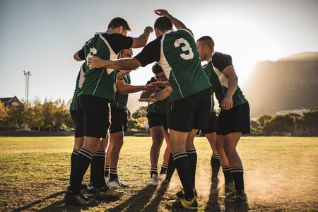 Rugby players cheering together after the game. Rugby team putting their hands together after winning the match.