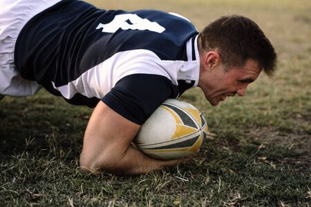 Strong rugby player with ball on ground during the game. Rugby player with possession of the ball in the match. Stock fotó - 127400707
