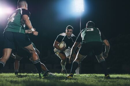 Rugby player running on field with ball and tackling with opposite team players during the game. Professional rugby action under lights at sports arena.