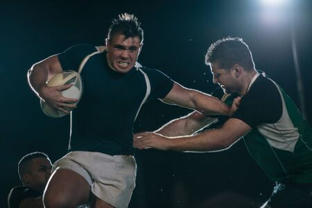 Rugby player throws opponent around with devastating stiff arms. Strong rugby player tackling opponent during the game. Stock Photo