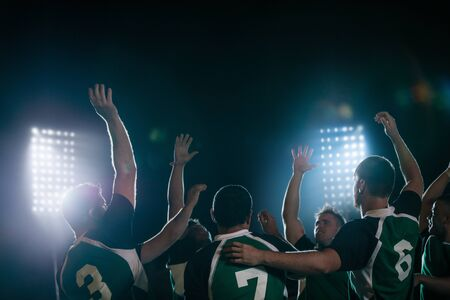 Group of rugby team player cheering the win at sports arena under lights. Rugby players celebrating victory. Imagens