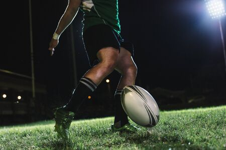 Rugby player drops the ball on the ground and then kicks it just as it bounces. Rugby player hitting a dropped goal under lights at sports arena. Imagens
