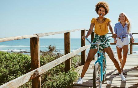 Young women enjoying with bike on boardwalk. Multi-ethnic female friends having fun with a bike at the seaside boardwalk.