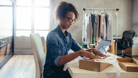 Woman online entrepreneur packing parcel box at office. Woman seller preparing product for delivery.