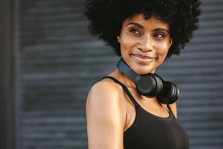 Fit young woman with a headphone smiling outdoors. Female jogger taking rest after a run looking away and smiling.