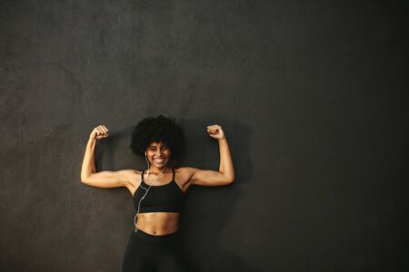 Strong woman flexing muscles and smiling against grey wall. African female model in sportswear showing her muscles n gym.
