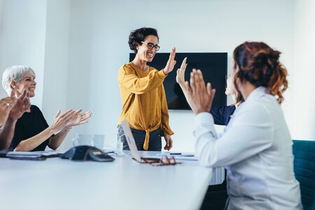 Happy business team in casual clothes at conference table  giving high fives to each other, celebrating success. Business team starting a new project.