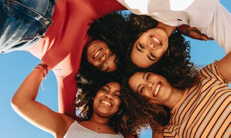 View from below of group of happy young girls with curly hair standing in circle and looking at camera. Smiling friends in a hurdle looking down. Stock Photo