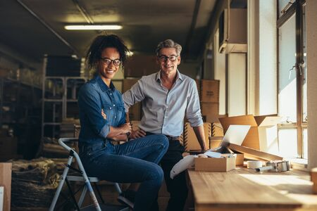 Portrait of man and woman standing in online store warehouse. Business partners together looking at camera and smiling.