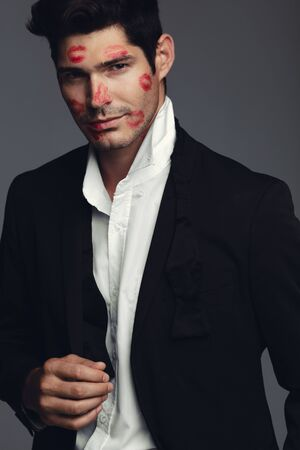 Stylish young guy covered with kiss marks on face. Good looking model standing against grey background.