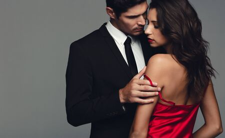 Pareja elegante en un momento sensual. Hombre y mujer románticos sobre fondo gris.
