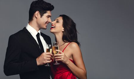 Happy young couple having champagne against grey background. Handsome young man and beautiful woman in stylish outfit having champagne and smiling. Stock Photo