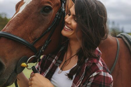 Close up of happy equestrian woman with a brown horse. Smiling cowgirl with her horse outdoors.