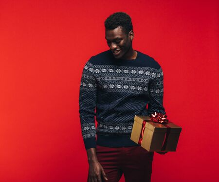 Young african guy holding a gift box. African american man with a present on red background.