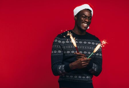 Cheerful young african man in santa hat celebrating with sparklers. Young guy enjoying with fireworks on red background