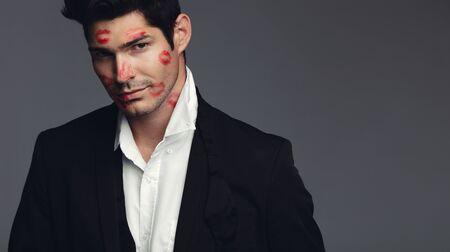 Stilvoller Mann mit Küssen auf dem Gesicht, das in die Kamera starrt. Hübscher Mann in stilvollen Casuals, der die Kamera vor grauem Hintergrund mit Kopienraum betrachtet.