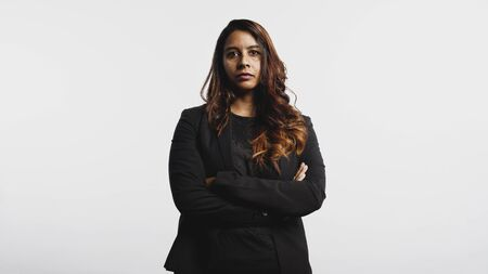 Young businesswoman standing against white background looking at camera. Portrait of businesswoman in formals standing with arms crossed.