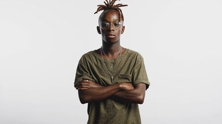 Serious looking african man with his arms crossed  isolated on white background. Portrait of young man with dreadlocks tied together looking at camera.
