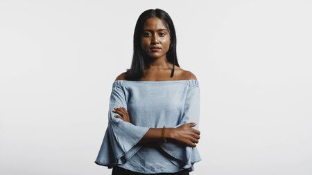 Portrait of woman with arms crossed looking at camera. Woman in fashionable denim top isolated on white background.