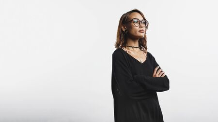 Portrait of woman standing with arms crossed looking away. Young woman in eyeglasses isolated on white background.