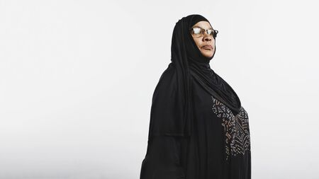 Senior muslim woman in hijab isolated on white background. Smiling arabic woman in eyeglasses and a black hijab looking away. 스톡 콘텐츠