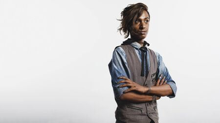 African man in waist coat isolated on white background. Fashionable man standing with arms crossed and looking away.