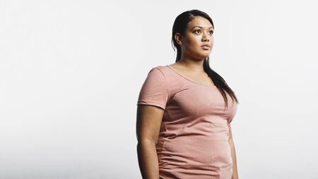 Woman in tshirt standing against white background. Portrait of obese woman looking away.