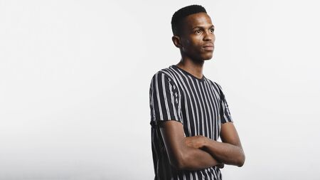 Portrait of african man looking away. Young man standing isolated on white background with arms crossed. 스톡 콘텐츠